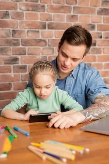 Довольный красивый молодой отец и его любопытная дочь сидят за столом и вместе используют мобильное приложение на смартфоне