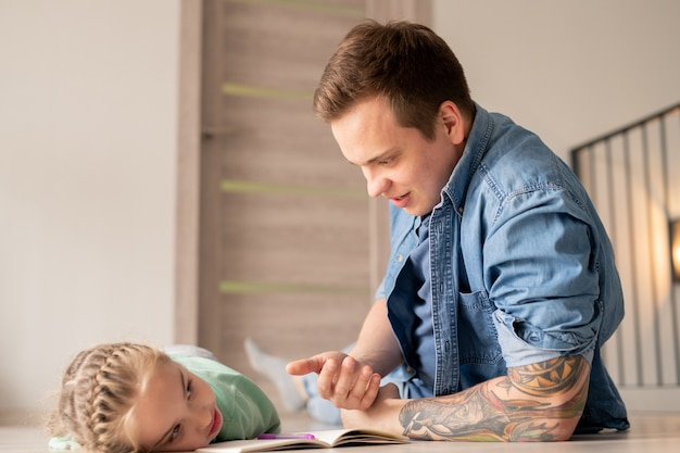 Content hipster father with tattoo lying on floor and talking to depressed daughter while inspiring and motivating her