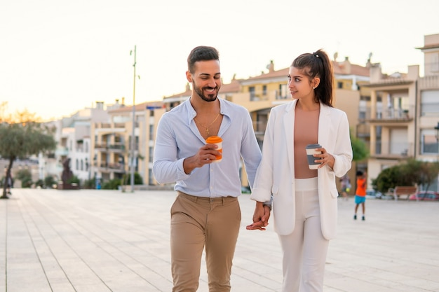 Content hispanic couple holding hands during stroll