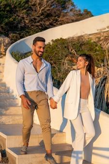Довольная латиноамериканская пара гуляет по лестнице в летнем парке