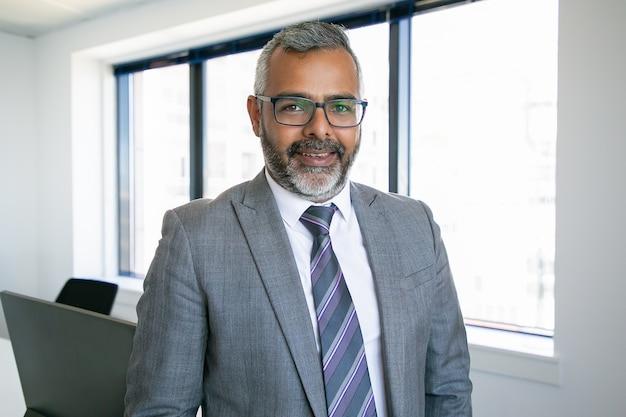 Содержание индийский генеральный директор стоит и улыбается портрету. успешный задумчивый бородатый бизнесмен в очках, позирует в офисной комнате. концепция бизнеса, выражения и управления