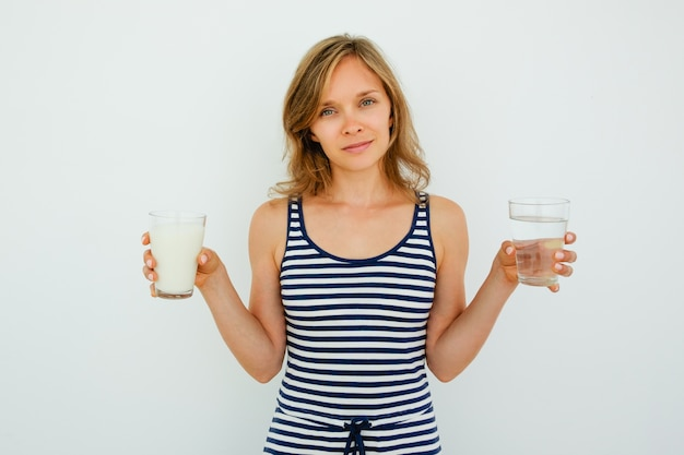 Content lady holding glasses of water and milk