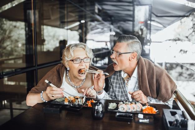 Довольные мужчина и женщина сидят на летней террасе, едят суши и счастливо проводят время вместе