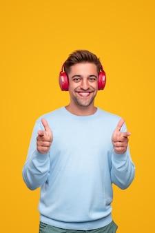 Довольный человек в наушниках, указывая на камеру с большими пальцами руки вверх