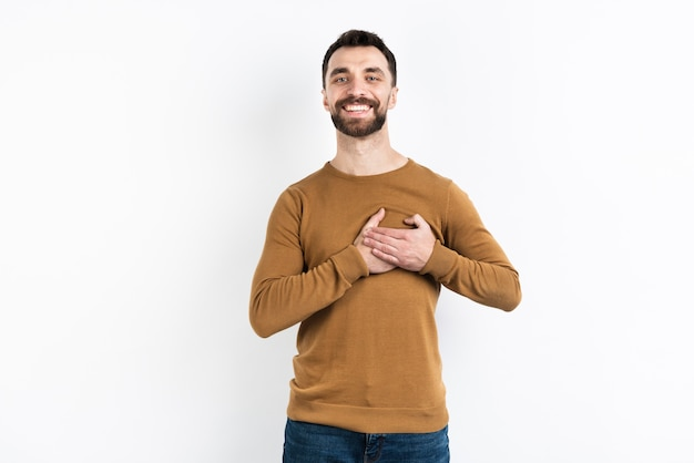 Content man posing while holding chest