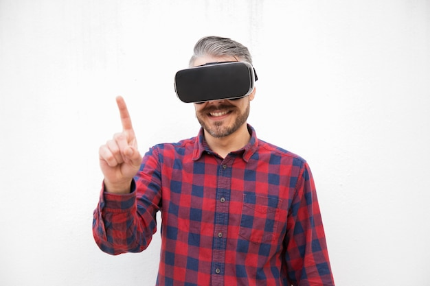 Content man in vr headset pointing with finger