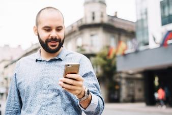 Content man watching phone at street