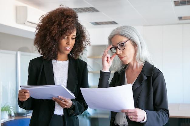 젊은 동료와 함께 문서를 읽는 안경에 콘텐츠 관리자. 통계 데이터를 공부하고 사무실 방에서 회의 두 성공적인 콘텐츠 경제인. 팀워크, 비즈니스 및 관리 개념