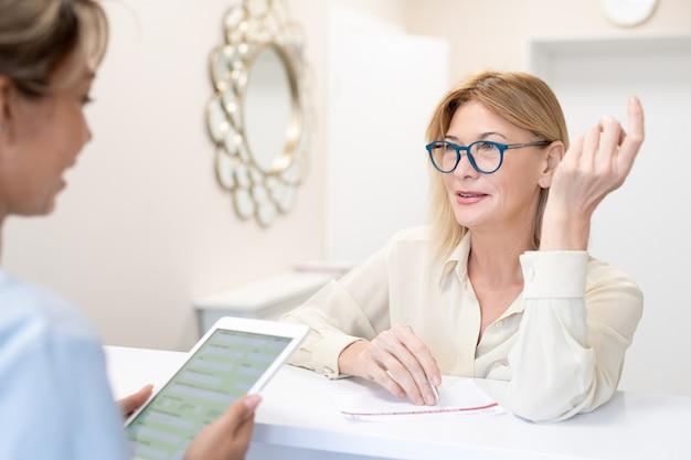 Довольная зрелая дама в очках стоит у стойки салона красоты и спрашивает администратора о косметической процедуре при заполнении договора