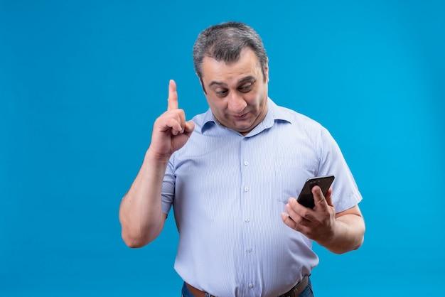파란색 줄무늬 셔츠에 콘텐츠 중년 남자가 파란색 공간에서 자신의 문제에 대한 탁월한 해결책을 찾는 휴대 전화를 찾고 있습니다.