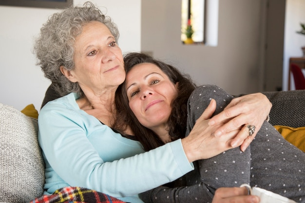 Content middle-aged daughter embraced by mother resting at home