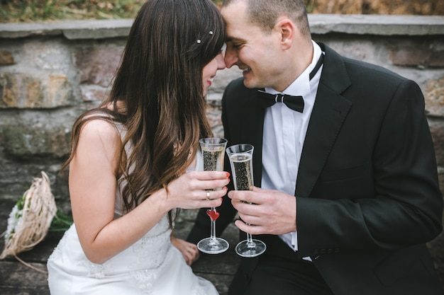 Content newlyweds posing with wineglasses