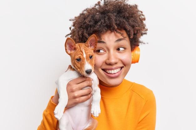 만족 한 아프리카 계 미국인 소녀 미소는 애완 동물과 함께 자유 시간을 보내고 행복하게 공원에서 산책하는 동안 작은 강아지를 얼굴에 부드럽게 안고 흰 벽에 고립 된 긍정적 인 감정을 표현합니다.