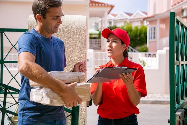 콘텐츠 우체국 직원이 고객과 이야기하고 야외에서 서 있습니다. 골 판지 상자를 들고 클립 보드와 듣는 배달원 남자. 택배 서비스 및 온라인 쇼핑 컨셉