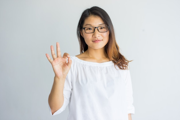 Content pretty asian girl with highlighted hair making ok sign as symbol of approval.
