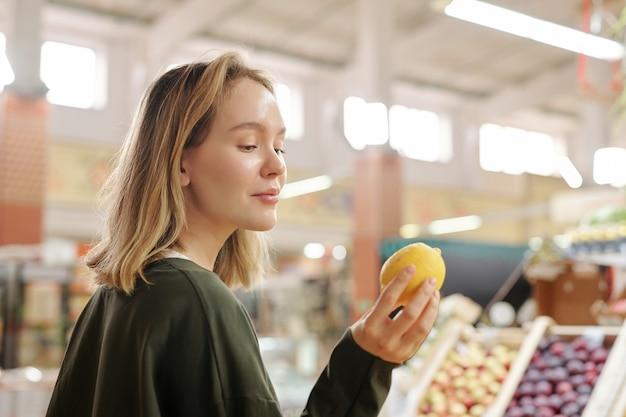 Довольная красивая девушка стоит на свежем рынке и смотрит на лимон, покупая его