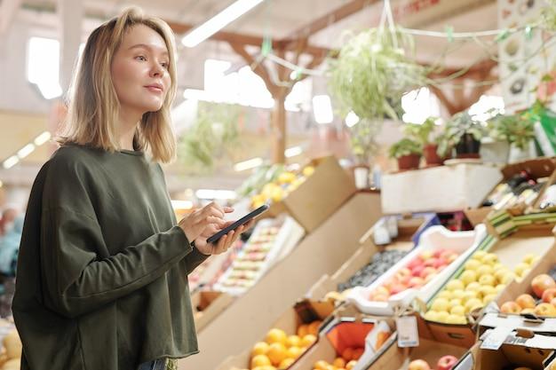 新鮮な市場に立って、それを購入しながら野菜を見ているコンテンツかわいい女の子