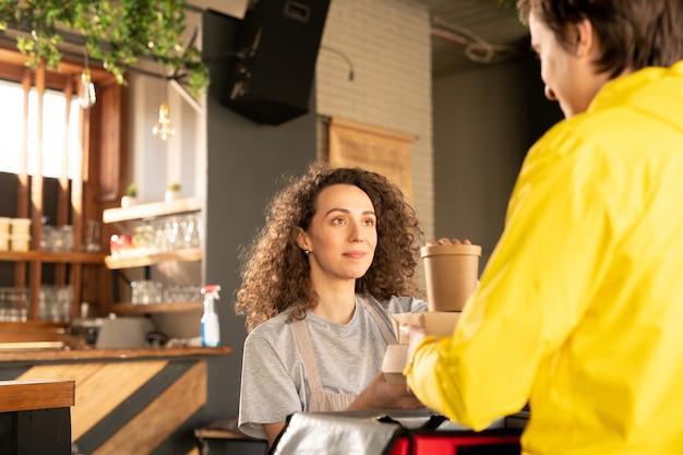 Довольная официантка с вьющимися волосами раздает упакованные коробки мальчику для доставки покупателю во время эпидемии коронавируса