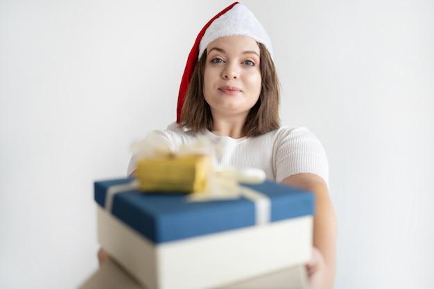 Довольная милая женщина в новогодней шапке дарит кучу рождественских подарков