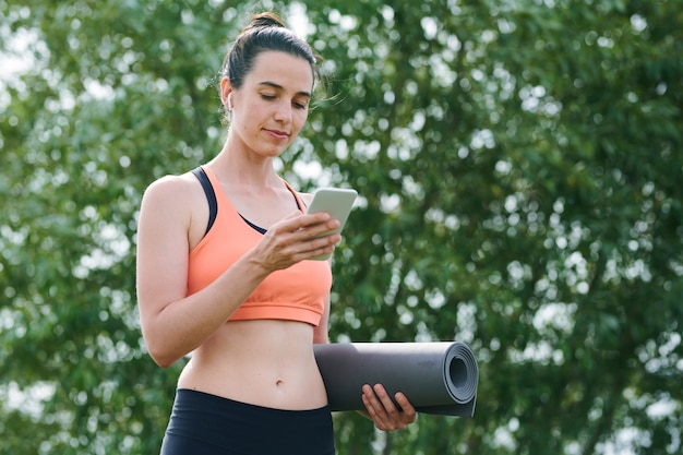 Content pretty woman in sports bra standing against tree in park and using phone while preparing for yoga practice outdoors