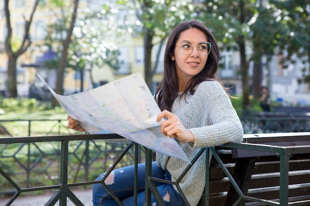 Content pretty young woman using paper map on bench outdoors