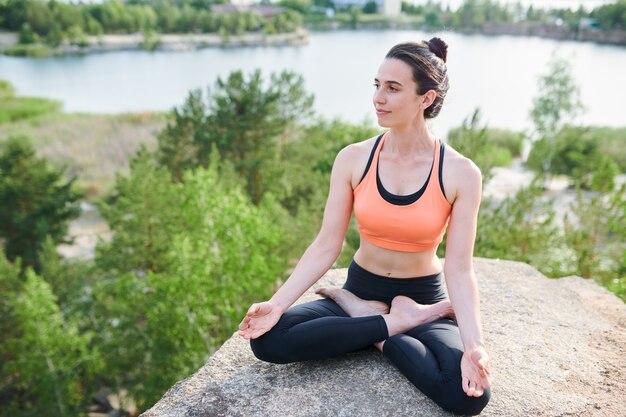 組んだ足を屋外で石の上に座って一人で瞑想するスポーツウェアのリラックスした若い女性