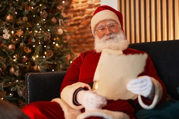 クリスマスツリーに対して肘掛け椅子に座って読書をしている赤い衣装のコンテンツサンタクロースは...
