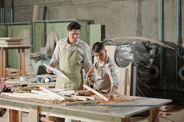 Content satisfied father with sketch looking at teenage son measuring wooden plank in woodworking studio