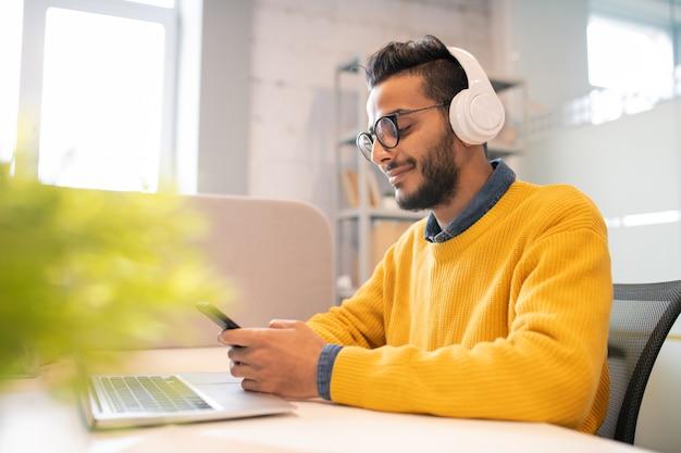 現代のオフィスに座っているひげとオフィスで働いている間スマートフォンでメッセージングで満足しているアラビアの若者
