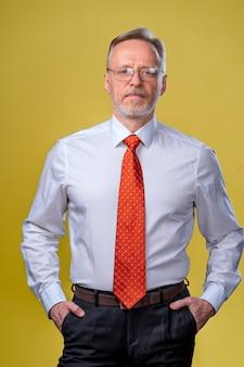 셔츠와 조끼에 콘텐츠 수석 비즈니스 사람입니다. 노란색 배경에 스튜디오에서 포즈. 자신감. 비즈니스 스타일 개념