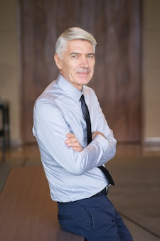 Content senior businessman with arms crossed