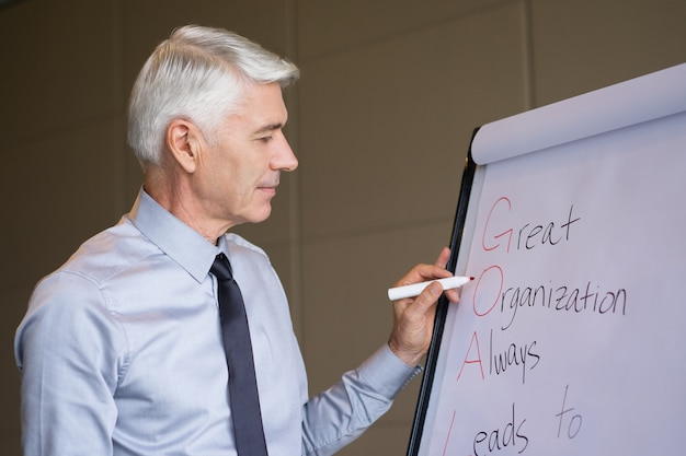 Content senior businessman writing on flipchart