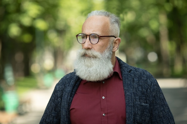 Content senior man with a beard and wearing glasses outdoor.