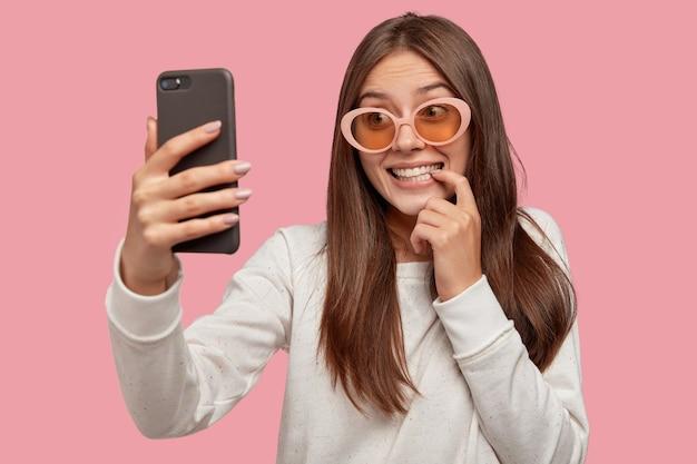 笑顔のヨーロッパの若い女性のコンテンツは、出会い系アプリで送信するためのスマートフォンを介して自分撮りを作ります