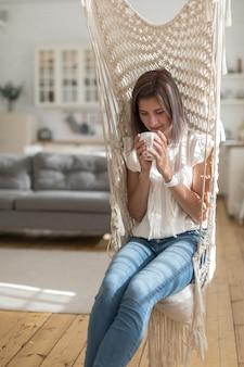 Довольная усмехаясь женщина держа кружку пока сидящ в деревенском заплетенном стуле качания в солнечной живущей комнате
