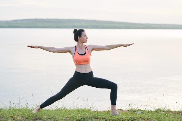 湖に対して草の上に立っている髪のパンと両腕平行地面を伸ばしてコンテンツスポーティな若い女性