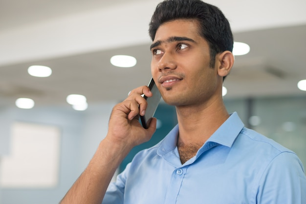 Content thoughtful young businessman using mobile phone