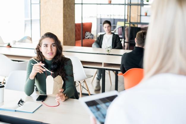 同僚と食事や会話をするコンテンツの女性