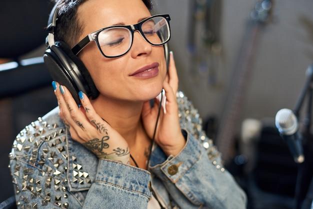 Content woman enjoying music in studio