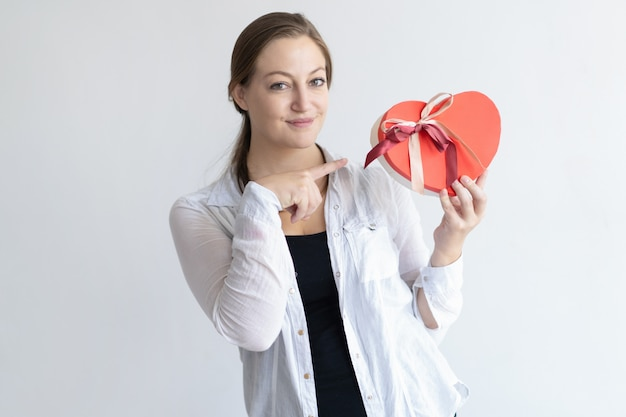 Content woman holding heart shaped gift box and pointing at it