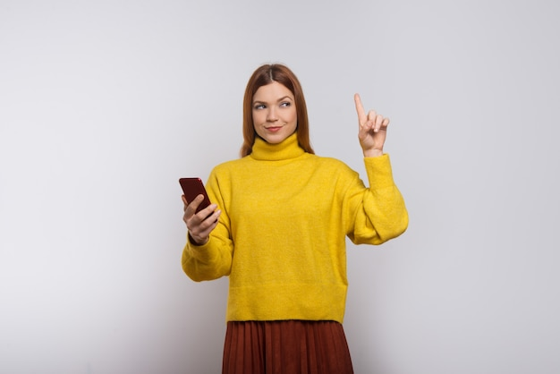 Content woman holding smartphone and pointing up