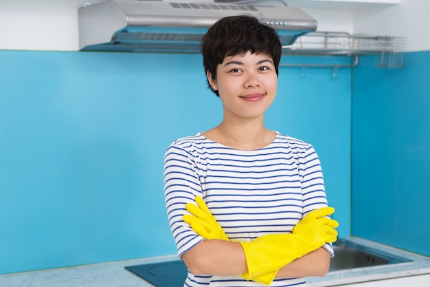 Content woman in protective gloves in kitchen
