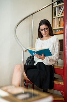 Content woman reading book in library