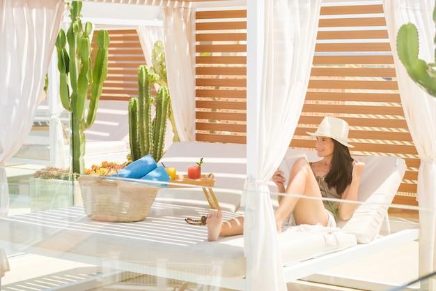 Содержимое женщины, читающей книгу на кровати с балдахином