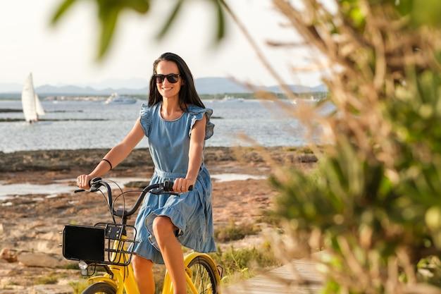 海岸沿いの自転車に乗るコンテンツ女性