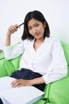 Содержание женщина, сидя в бинбэг с ручкой