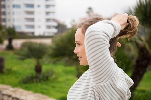 Довольная женщина завязывает волосы в хвост и носит спортивную одежду