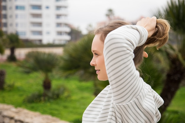 Content woman tying hair in ponytail and wearing sportswear
