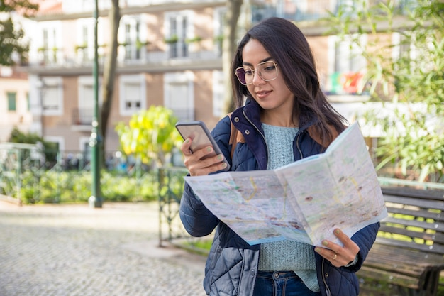 Content woman using paper map and smartphone outdoors