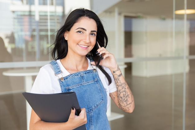 Content woman with folder talking by smartphone